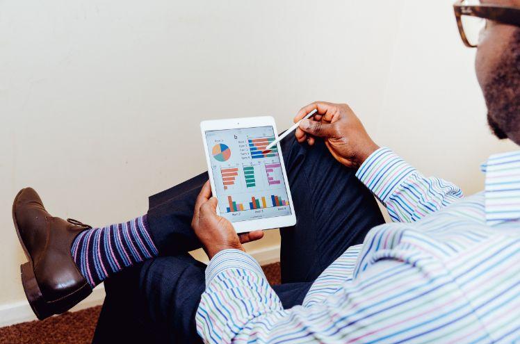 Persona sentada mirando analíticas en un ipad