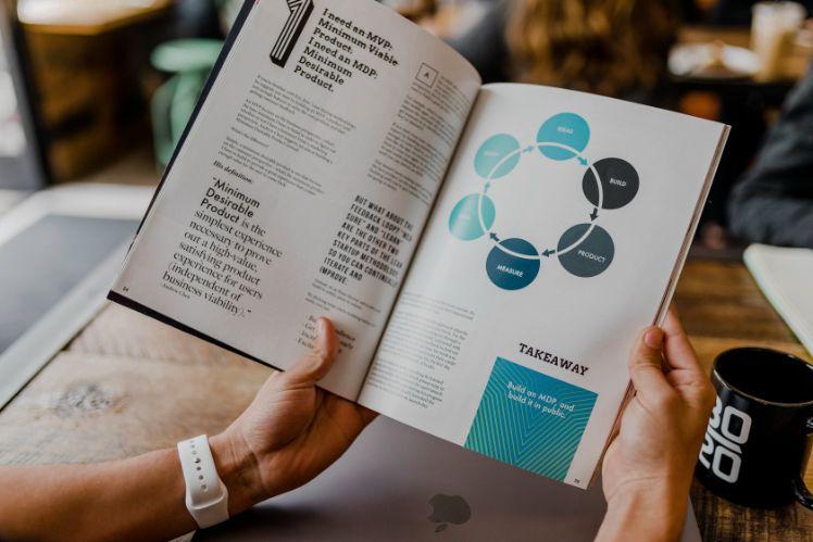 manos sosteniendo un libro sobre estrategias de negocios